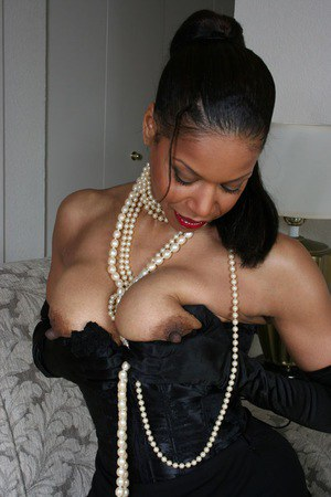 Ebony mature Semmie Desuora revealing her melons from a classy corset dress