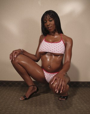 Ebony babe with big tits Erika Vution poses to show her oiled body