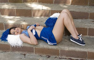 Sexy cheerleader spreading her legs and rubbing her slit outdoor