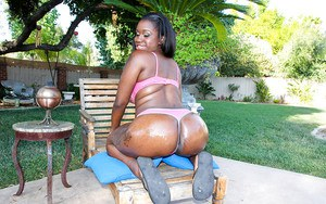 Busty ebony babe with big ass Black Swan posing and stripping outdoor