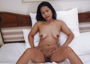 Asian mature woman with big flabby tits stripping and posing on the bed