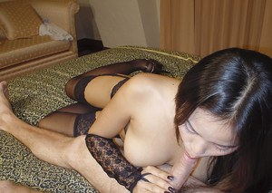 Busty asian babe in black stockings gives a blowjob and gets slammed