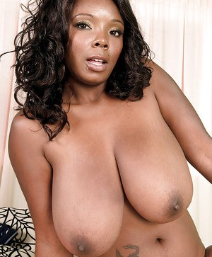 Ebony MILF on high heels uncovering her big tits and giving a blowjob