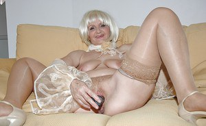Sexy granny in stockings strips naked to feel her cunt with a big toy
