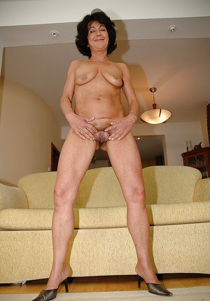 Granny with a slender body poses on high heels and shows her wet hole