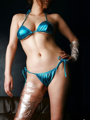 Kinky asian babe in bikini covering her sexy body with cellophane