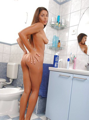 Alluring brunette babe with big tits posing naked in the bath