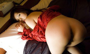 Horny asian babe with petite tits teasing her hairy slit on the bed