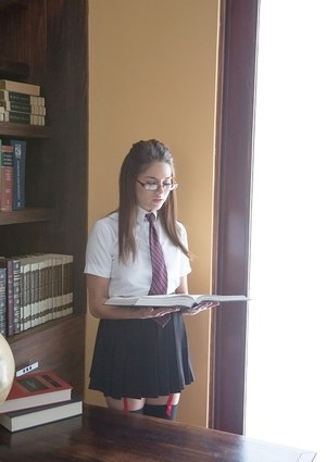 Seductive teenage brunette slipping off her school uniform