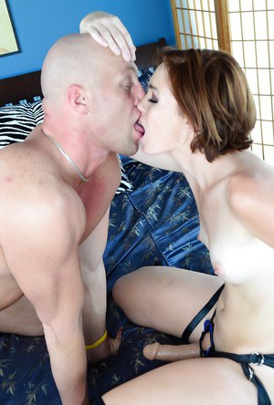 Jodi Taylor strokes a bald guy's cock while fucking him by a strapon