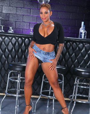 Tattooed ebony MILF with huge jugs and big butt getting naked