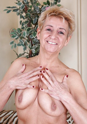 Lustful blonde granny stripping and exposing her hairy private parts