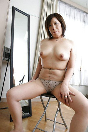 Asian MILF in pantyhose Kimiko Ogata stripping off her suit and lingerie top