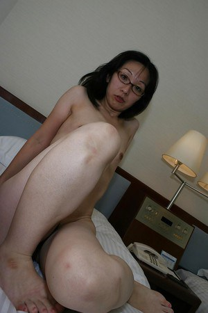 Skinny asian MILF in glasses undressing and exposing her twat in close up