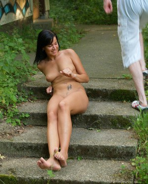 Seductive brunette amateur with long legs posing naked outdoor