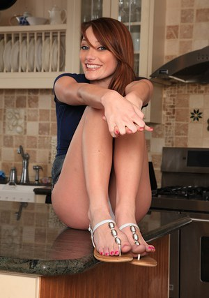 Desirable redhead hottie makes some hot creamy action in the kitchen