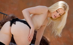 Amazingly lovely blonde in black nylons exposing her slim curves outdoor