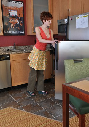 Short-haired redhead amateur slowly uncovering her goods in the kitchen