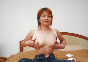 Adorable asian girl in jeans undressing her tight body and tits
