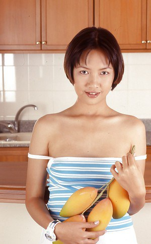 Clothed Asian with tiny tits is posing in the kitchen with spread legs