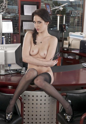 Brunette secretary is posing in the office and playing with big tits