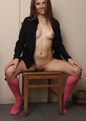 Teen with skinny shape Kira is sitting on the chair with spread legs