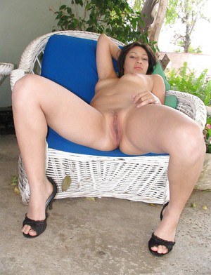 Tanned Latina Sonia A poses on her black high heels in the garden
