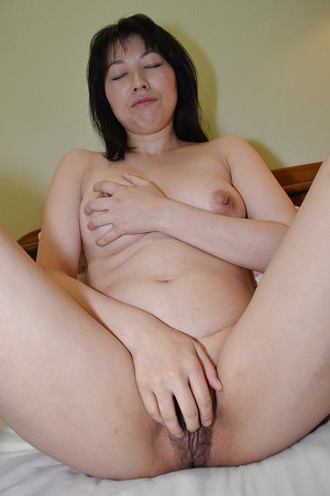 Asian model Shigeko Yokoi slowly takes off her clothes on the bed