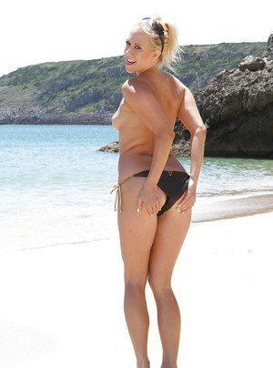 Topless blonde babe shows off her perfect figure in solo poses on beach