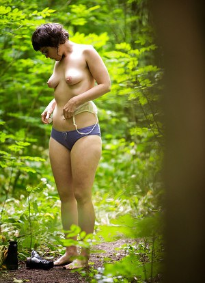 Voyeur snaps of naked brunette chick in glasses getting dressed in woods