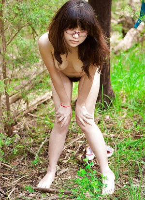 Petite Asian girl in glasses bares hairy vagina outdoors after slow strip
