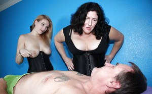 Two horny femdom MILFs with big tits giving some guy a painful handjob