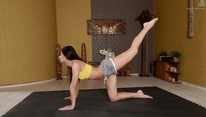 Fully clothed Euro brunette Aruna Aghora doing yoga in barefeet and shorts