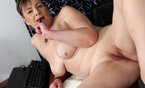 Mature woman Sandra Green flashing cleavage and shaved vagina at work