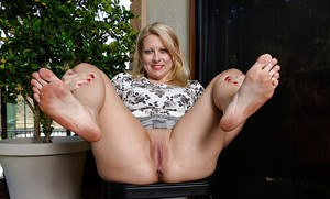 Mature blonde Zoey Taylor playing with barefeet and flashing bald cunt
