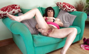 Mature solo broad Christina X unveiling hairy vagina on couch