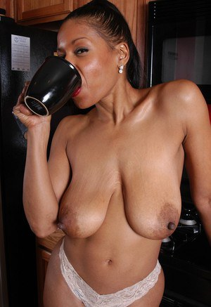 Older black chick Semmie undressing for nude photo session in kitchen
