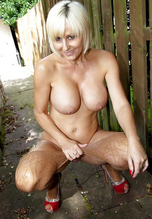 Busty blonde pantyhose adorned lady Jan Burton spreads shaved cunt outdoors