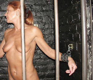 Mature submissive woman Lady Sarah poses in variety of restraining devices