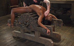 Pretty ebony coed Ana Foxxx is attached to rack for painful sex games