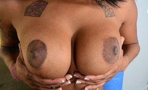 Tattooed ebony chick releasing big natural black juggs while undressing