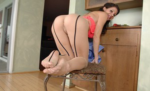 Brunette MILF Angel Little rolling down pantyhose to reveal shaved pussy