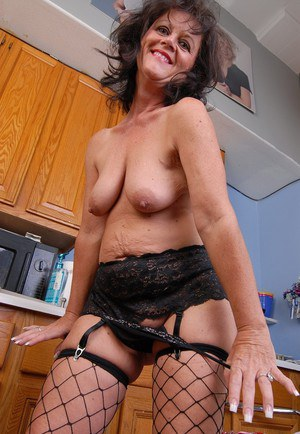 Mature brunette Debella flaunting big thong attired butt in kitchen