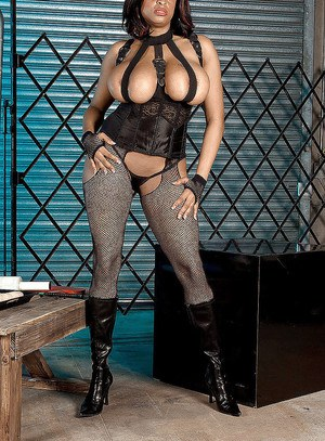 Buxom ebony babe Carmen Hayes struts in boots and corset with riding crop