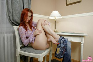 Redhead teen babe Gabriella E removes jeans and panties before masturbating