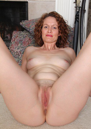Clothed mature dame Ajia Simpson undressing for spreading of pussy