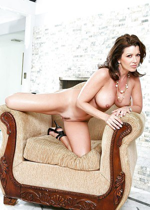 Busty brunette pornstar Raquel Devine showing off mature ass in high heels