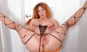Mature redhead with great legs freeing hairy cunt from panties