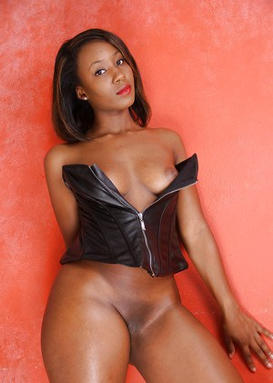 Mature black lady Chiya stripping off leather lingerie to pose naked