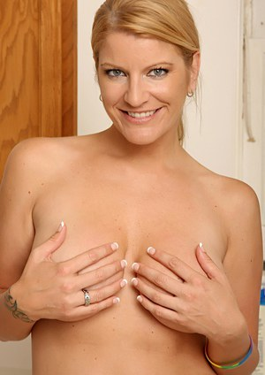 Blonde MILF Robbye Honeck revealing large all natural boobs in kitchen